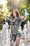 Attractive girl in black transparent veil playing with water in a summer hottest day. Wet girl enjoying fountains. Young woman Royalty Free Stock Photos