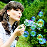Attractive girl blowing soap bubbles. In summer green park Stock Photos