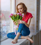Attractive girl with bouquet of tulips on window-sill. Young attractive girl in blue jeans sitting with bouquet of tulips on window-sill royalty free stock image