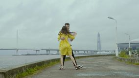 Attractive girl and boy dance emotionally some retro dance on rain pools of a pier stock video footage