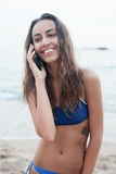 Attractive girl brunette blue bathing suit talking cell phone beach Stock Photography