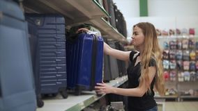 Attractive girl buys luggage. stock video