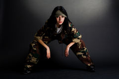 Attractive girl in camouflage. Posing against dark background Royalty Free Stock Photo