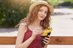 Attractive girl in casual clothes sits with ice cream at wooden bench and posing into camera. Young student female having rest stock image