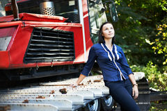 Attractive girl about caterpillar tractor Royalty Free Stock Photography