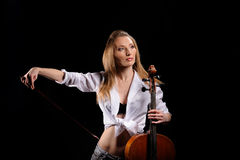 Attractive girl with cello isolated. Over black background royalty free stock photos