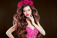 Attractive girl with chaplet of roses on head, long wavy hair st. Yling, sensual lips. Fashion lady isolated on dark background Royalty Free Stock Photos