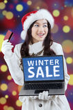 Attractive girl in christmas hat online shopping Royalty Free Stock Images