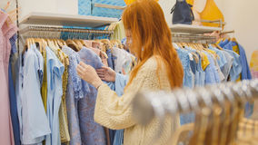 Attractive girl in a clothing store chose a dress - shopping concept. Close up Royalty Free Stock Image