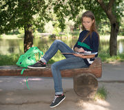 Attractive girl college student reading a book on bench in the park. Stock Images
