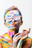 Attractive girl with colorful bright body art and sunglasses sending air kiss. Isolated on white stock photo