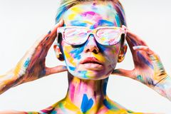 Attractive girl with colorful bright body art and sunglasses touching head. Isolated on white stock image