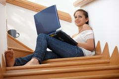 Attractive girl with computer at stairs Royalty Free Stock Image