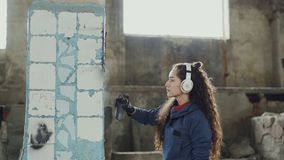 Attractive girl is concentrated on decorating old dirty column with graffiti in abandoned building using aerosol paint. Young woman is listening to music with stock video footage