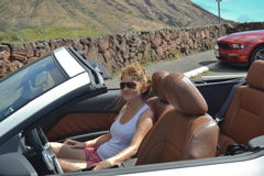 Attractive girl in a convertible car. Close up action capture of an elegant blond sexy girl with sunglasses in a sports convertible car Stock Photography
