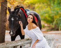 An attractive girl cuddles to the horse. Outside. In the autumn. Royalty Free Stock Photos