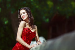 Attractive girl with curly long hair in red dress. Sexy woman. Hollywood star. Fashionable teen posing at day park Stock Photos