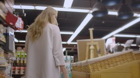 Attractive girl customer is buying bread in bakery department is shop, smelling it, smiling and putting in shopping. Trolley. Healthy lifestyle and supermarket stock video footage