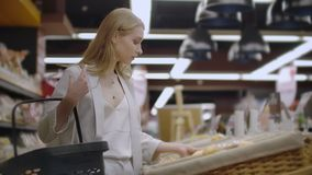 Attractive girl customer is buying bread in bakery department is shop, smelling it, smiling and putting in shopping. Trolley. Healthy lifestyle and supermarket stock video