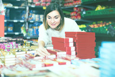 Attractive girl customer looking for tasty sweets in supermarket Royalty Free Stock Image