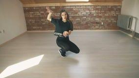 Attractive girl dancing twerk at brown studio background. Beautiful athletic girl in black dancing booty dance twerk in studio sitting on floor on brown stock footage