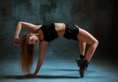 Attractive girl dancing twerk in the studio. Attractive girl dancing twerk iat the blue studio background stock image