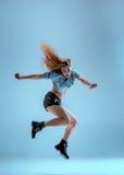 Attractive girl dancing twerk in the studio. Attractive girl dancing twerk iat the blue studio background stock photo