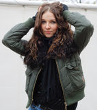 Attractive girl with dark hair. Attractive girl with long dark hair and wintry jacket or coat outdoors; wall in background Stock Photos