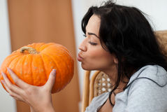 Attractive girl with dark hair kissing pumpkins Royalty Free Stock Photo