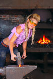Attractive girl in dirty workshop with hamer Stock Image