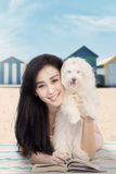 Attractive girl with dog and book at shore. Photo of attractive young girl with long hair, smiling at the camera with a book and dog at shore Stock Images