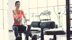 Attractive girl doing exercises with simulator in the gym stock video footage