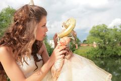 Attractive girl and doll Royalty Free Stock Photography