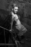 Attractive girl in dress posing in the slums. Beautiful chick standing on the grungy stairs Royalty Free Stock Images