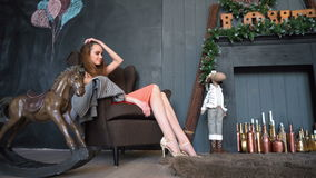 Attractive girl in dress sitting in armchair in cozy room, together with the rocking horse stock footage