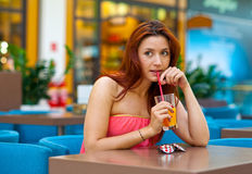 Attractive girl drinking juice in bar Royalty Free Stock Images