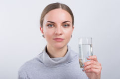 Attractive girl drinking water on light background royalty free stock photos
