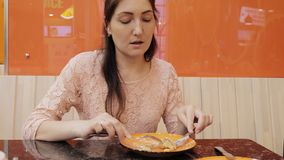 Attractive girl eating a pancake with ice cream in cafe, close up.  stock footage