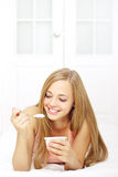 Attractive girl eating yogurt Stock Images