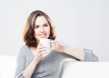 Attractive girl enjoying a cup of coffee at home Stock Photography