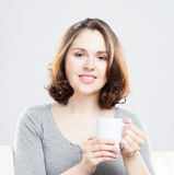 Attractive girl enjoying a cup of coffee at home Royalty Free Stock Image