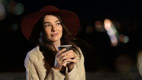 Attractive girl enjoying cup of coffee at night stock video
