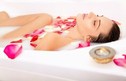 Attractive girl enjoys a bath with milk. Attractive naked girl enjoys a bath with milk and rose petals. Spa treatments for skin rejuvenation Stock Photo