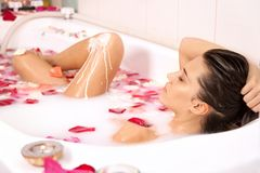 Attractive girl enjoys a bath with milk and roses royalty free stock images