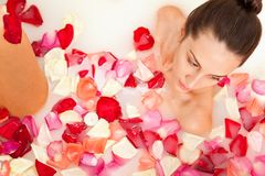 Attractive girl enjoys a bath with milk and roses Royalty Free Stock Image