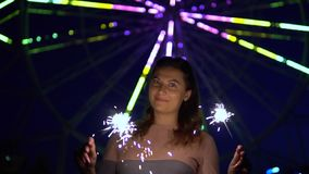 An attractive girl enjoys the holiday with fireworks in her hands having a good mood. slow motion. An attractive happy girl is happy with a holiday with stock video footage