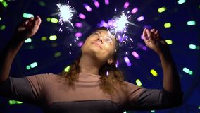 An attractive girl enjoys the holiday with fireworks in her hands having a good mood. slow motion. HD. An attractive happy girl is happy with a holiday with stock video