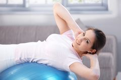 Attractive girl exercising on fit ball smiling Stock Images