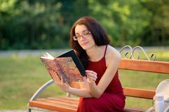 Attractive Girl in Eyesglasses and Long Red Dress is Sitting on the Bench in the City Park, Reading Some Book and. Smiling royalty free stock images