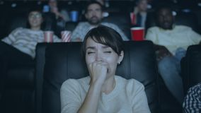 Attractive girl feeling scared during horror film in dark modern cinema. Attractive girl is feeling scared during frightening horror film sitting in comfortable stock video footage